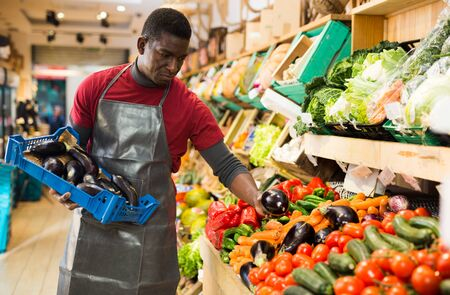Experienced African American salesman filling counter of vegetable department of supermarket with fresh eggplants Imagens