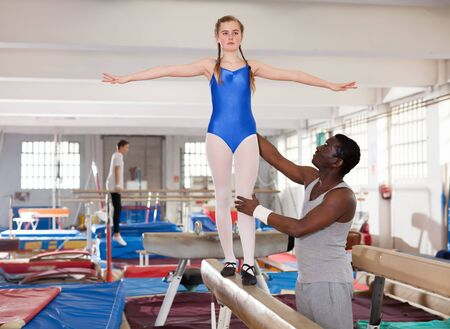 Glad African male coach helping teenage girl doing gymnastic exercises on equipment