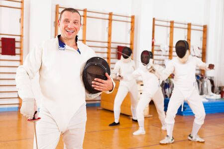 Sporty young man fencer in uniform standing with mask and foil at the fencing workout Stock Photo