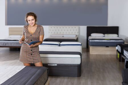 Portrait of modern girl testing quality of new mattress for bed in salon, looking at catalog Stock fotó