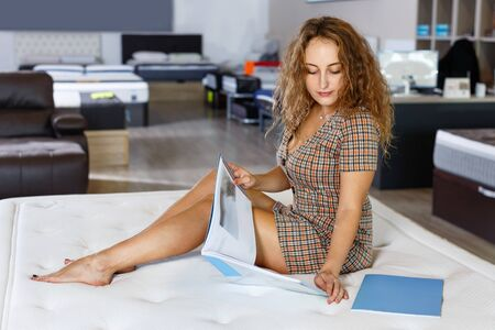 Young glad pleasant positive attractive woman choosing right mattress with booklet in home furnishings store