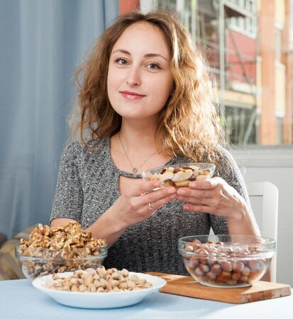 Portrait of positive woman holding walnuts, hazelnuts and pistachios at home