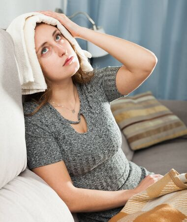 Woman with wet towel on her forehead suffering from headaches at home