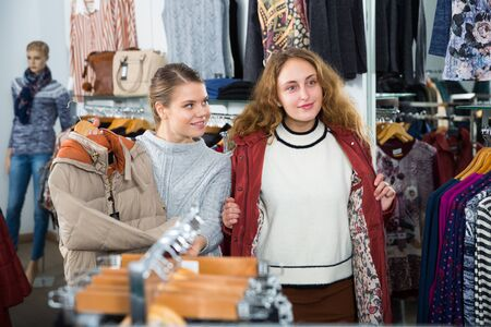 Two cheerful women trying coat in outerwear clothing boutique