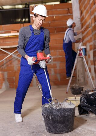 Asian and Hispanic workers in work wear doing repair work inside built cottage