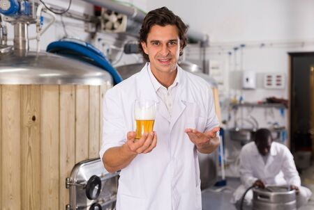 Young man brewer in uniform is standing with glass of beer in brew-house