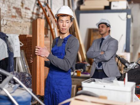 Strict male chief supervising quality of work of employee at building