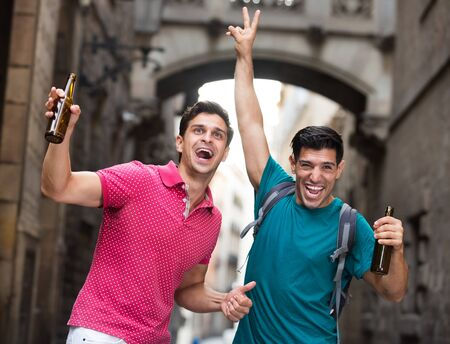 Portrait of two smilling football fans with beer who are celebrate win of teem in matcn at the Barcelona