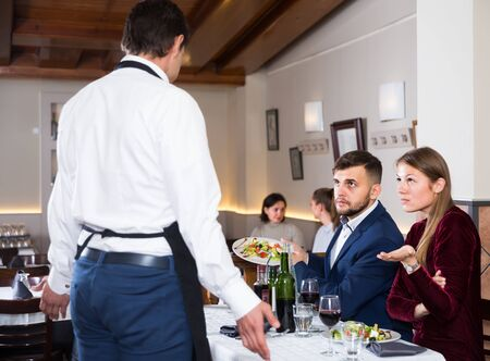 grumpy guests conflicting with waiter because of poor quality of dish in restaurant