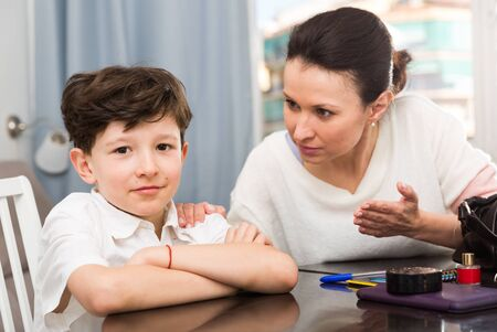 Smiling preteen boy sitting at home table while mother reprimanding him