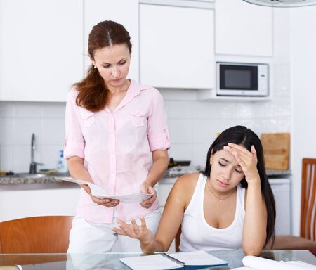 Mother upset because her daughter is not studying well, scene in kitchen Standard-Bild