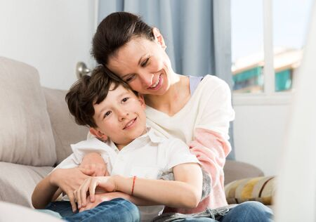 Happy family of young mother and preteen son spending time together at home Фото со стока