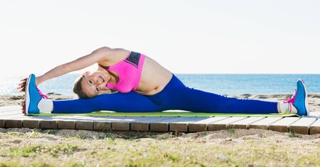 Positive adult woman practicing set of stretching for split in nature
