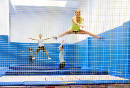 View of yellow safety net in trampoline sports center with blurred young people training on background