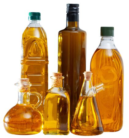 Fresh olive oil in bottles on wooden table. Isolated over white background
