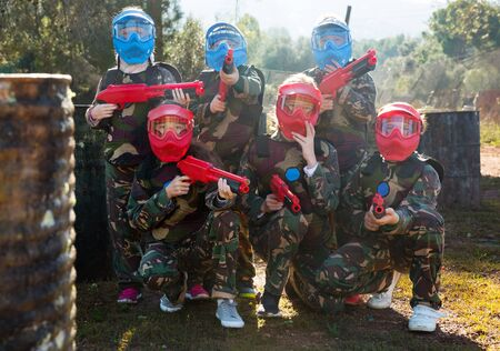 Portrait of team of boys and girls paintball players with marker pistols ready for game outdoors