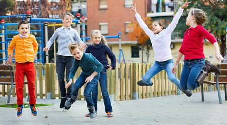 Happy laughing positive kids having fun and jumping up
