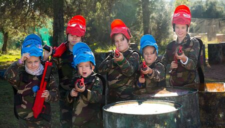 Group of boys and girls paintball players with marker pistols ready for game outdoors
