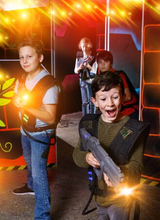 Emotional happy cheerful teen boy with laser pistol playing laser tag with friends on dark labyrinth