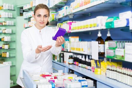 Woman pharmacist is attentively looking medicines in lockers in pharmacy Stockfoto