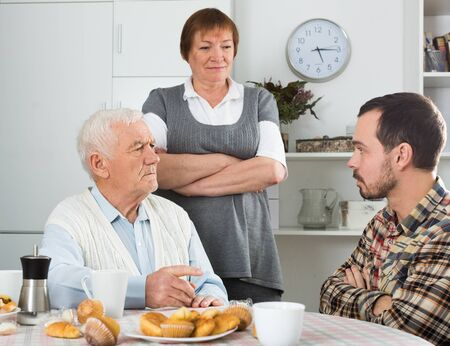Elderly grandfather teaches his grandson in presence of grandmother