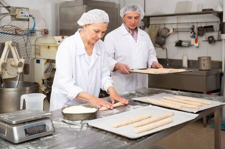 Experienced middle aged woman working with male assistant in bakery, forming baguettes from raw dough