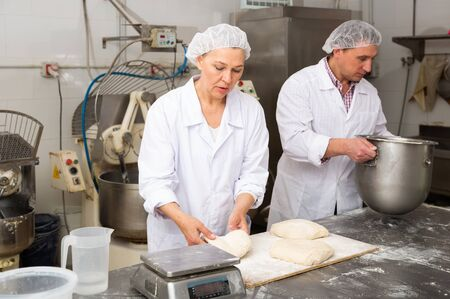 Mature woman professional baker standing at work table and forming dough for baking bread