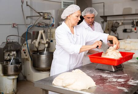 Bakers weigh the dough on the scales
