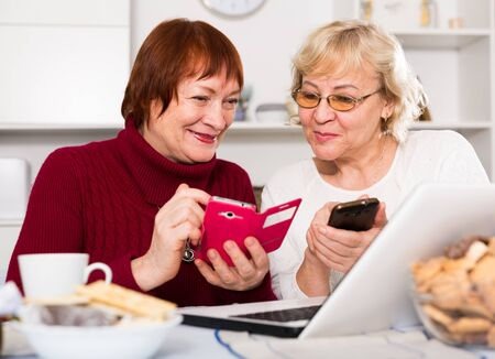 Two smiling elderly women sitting at home table with laptop using phones