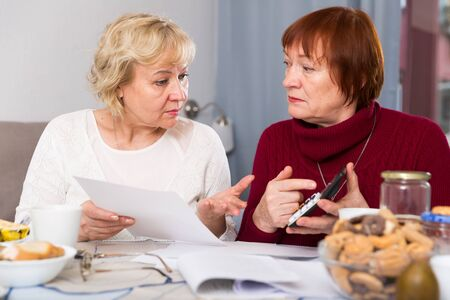 Two elderly women faced financials troubles, sitting at table with bills and calculator Stock Photo