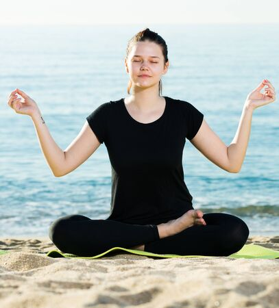Sportswoman in black T-shirt is sitting and practicing yoga near sea.