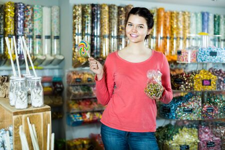 Smiling girl showing selected sweets in a candy store