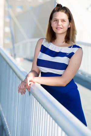 Young positive girl in blue dress standing on modern city bridge