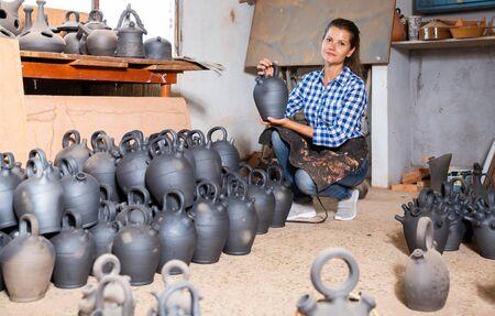 Portrait of cheerful female potter inspecting black ceramic bottle in pottery studio