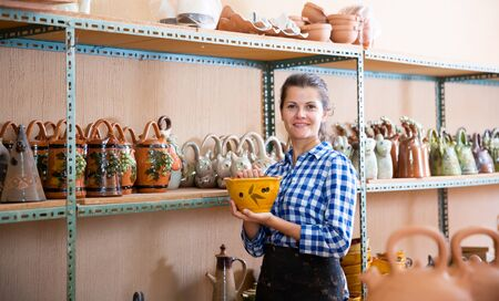 Portrait of young woman demonstrating finished production in pottery workshop