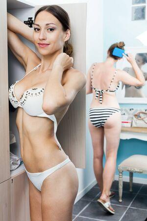 Beautiful young girl in bikini undressed after swiming pool in spa salon locker room Stock Photo