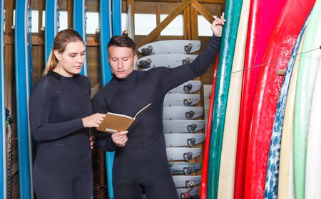 Young woman talking to athletic man while taking for rent a surf equipment in a surf club. Focus on both persons