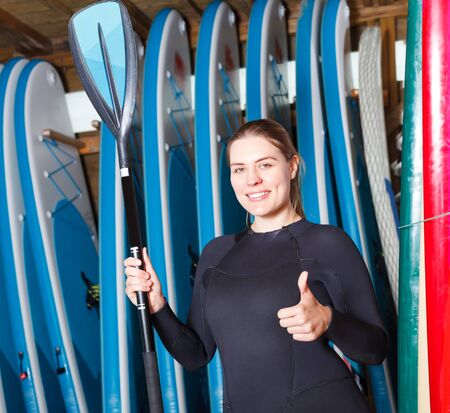 Adult woman surf club instructor wearing water suit, standing next to paddle boards Foto de archivo