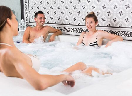 Young happy people relaxing in hot tub in spa Archivio Fotografico