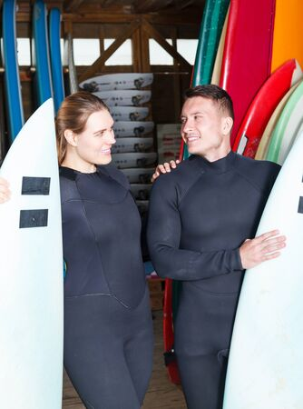 young people in wetsuits standing with surfboards in beach surf club