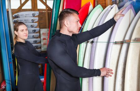 Young man and woman dressed surfing suits checking surfboards on racks in the surf club. Focus on man
