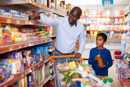 Happy friendly pleasant African family of father and tween son shopping together in supermarket Archivio Fotografico
