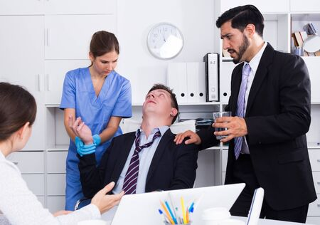 Man receiving first aid from female doctor and coworkers in office