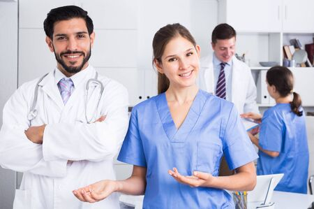 Portrait of young female doctor with male colleague inviting in clinic