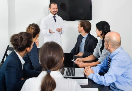 Positive efficient scientist presenting report during working meeting in office