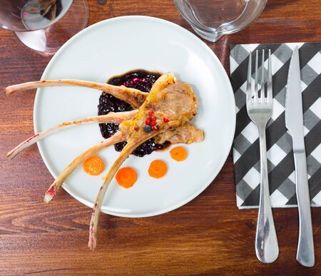 Top view of baked rack of lamb served on white plate with carrots in delicate berry sauce on wooden background 版權商用圖片