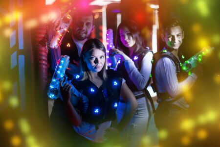 Group portrait of young people in colorful beams of laser guns having fun on lasertag arena