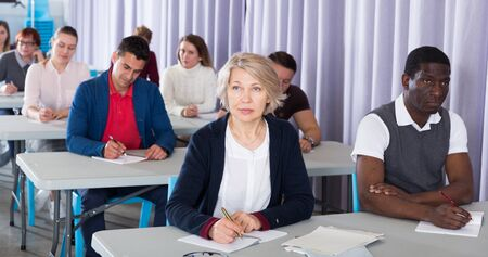 Multinational group of adult students listening teacher in classroom