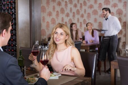 Young woman with male colleague on friendly meeting over dinner with wine in restaurant