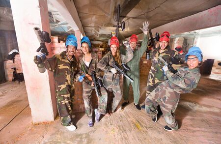 Portrait of friends who are satisfied by the game in the paintball club